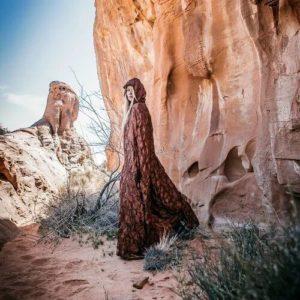 women in cape, red rocks,